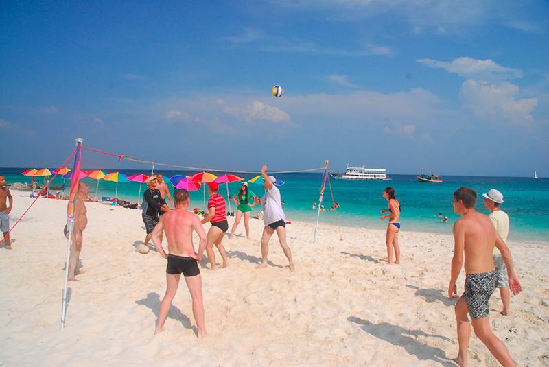 народ отдыхает играя в волейбол на одной из морских экскурсий