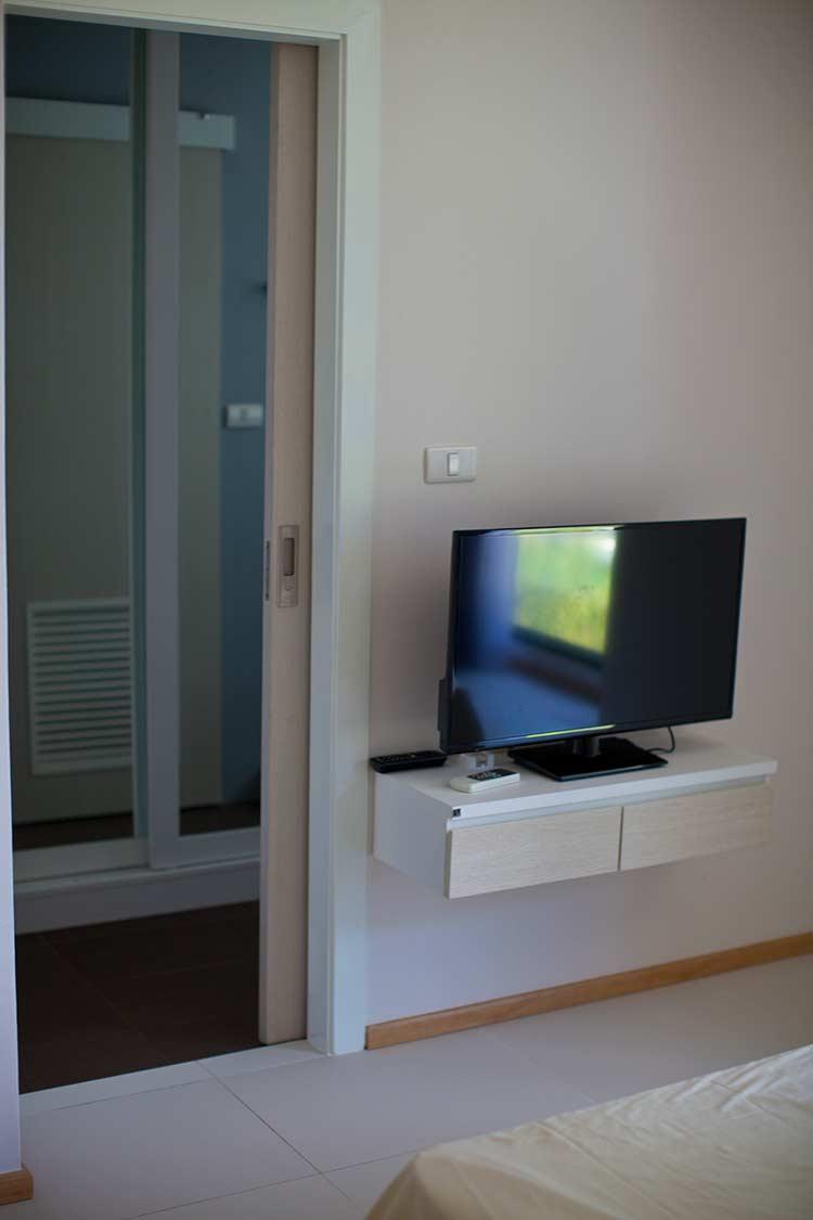 за телевизором виден небольшой кусочек гардероба