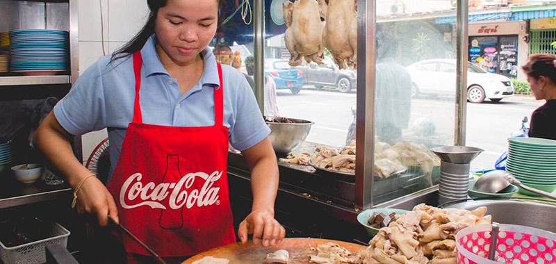 Девушка готовит Кхао Ман Гай в Тайланде